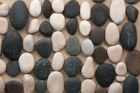 Black and white stones lay in rows on the sand
