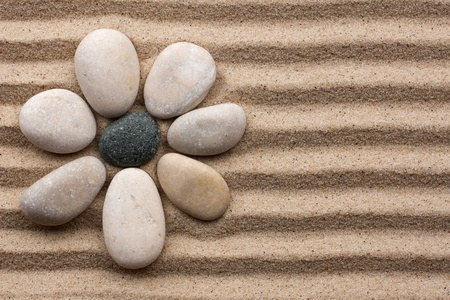 traditional wellness: Stone flower on a background of sand