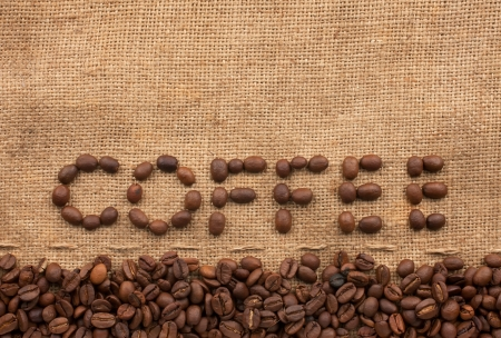 The word coffee made from coffee beans on sackcloth next to coffee beans Archivio Fotografico