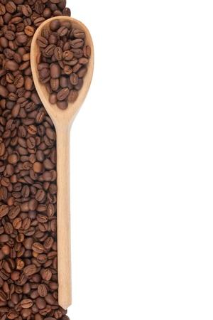 grains of coffee: Cuchara de madera con los granos de caf� aislados en el fondo blanco Foto de archivo