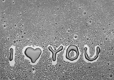carta de amor: Inscripci�n Te amo escrito en un fondo negro con agua Foto de archivo