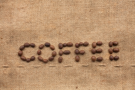 The word coffee made from coffee beans on sackcloth next to coffee beans photo