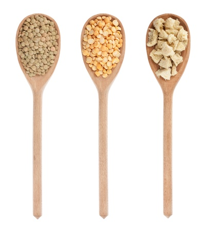 lentils, peas, soy  in three wooden spoons, isolated on white