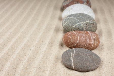 stones laid out in a row on the sand background Stock Photo - 16878833