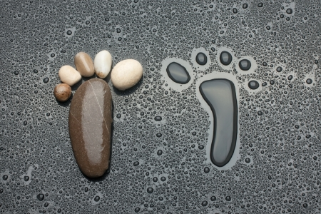 The footprint made up of water and rocks on a black background photo