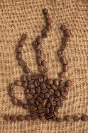 Coffee cup made of coffee beans on a burlap can be used as background