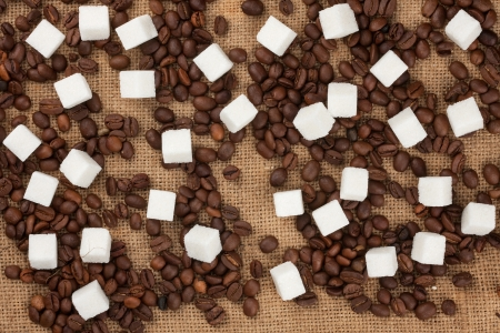Lump sugar and coffee beans on sackcloth can use as background photo