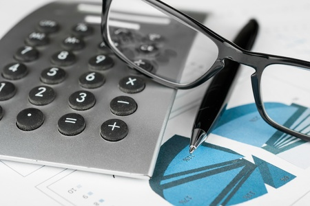 Pen, calculator and glasses on a background of diagrams Business concept  photo