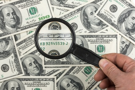 Hand with magnifying glass on a background of money  Concept Stock Photo