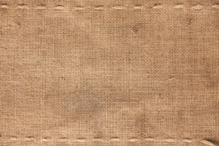The two horizontal stitching on the burlap as background Archivio Fotografico