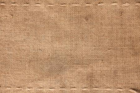 La costura dos horizontales en la arpillera como fondo