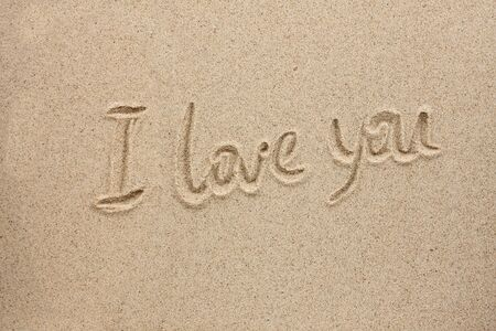The word i love you written on the sand, as the background  photo