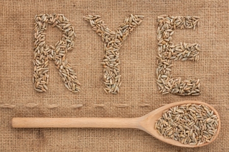 Inscription rye with a wooden spoon on burlap can be used as background photo