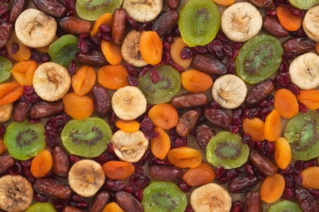 Dried apricots, kiwi, figs, dates, cranberries on sackcloth can use as background as a background photo