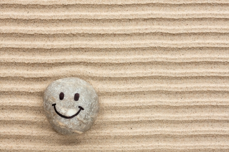 Smiley stone lying on the sand