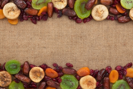 Mixture of dried fruits lying on sackcloth space for text photo