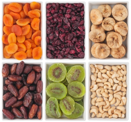 Nuts and dried fruits in ceramic plate, isolated on white background Stock Photo
