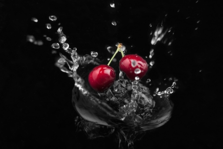 Cherry falling into the water on a black background Zdjęcie Seryjne