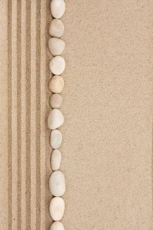 Stripe of white stones lying on the sand with space for text photo