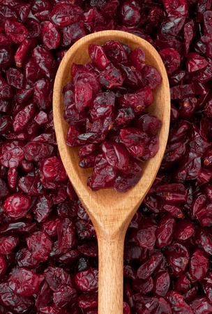 Wooden spoon with dried cranberries lies on the cranberries