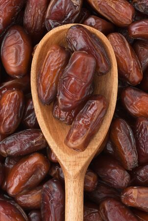 dates fruit: Wooden spoon with dried dates lies on the dates