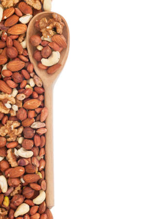 Wooden spoon with nuts, isolated on a white background photo
