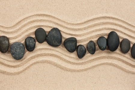 Black stones on the sand, can be used as background