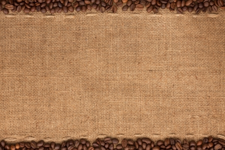 Coffee beans lying on sackcloth with space for text photo