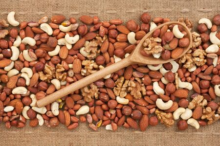 Wooden spoon with  nuts,   lying on sackcloth photo