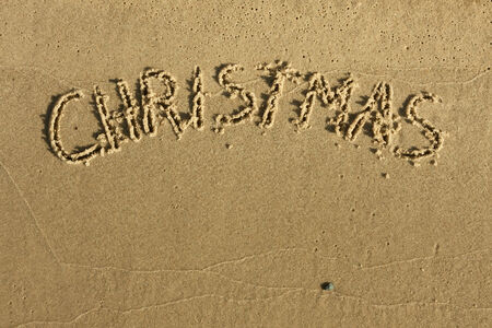 The word Christmas written on sand   photo