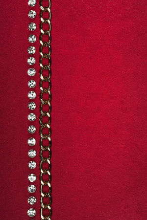 Gold chain and rhinestones lying on red fabric  photo