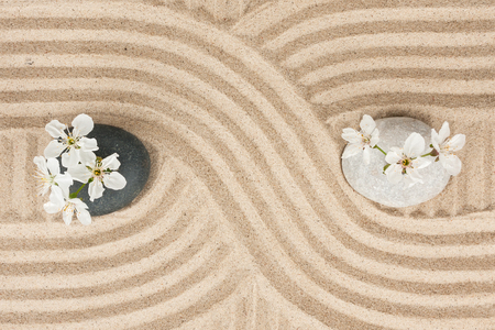 Black and white stone with flowers on the sand, as the background photo