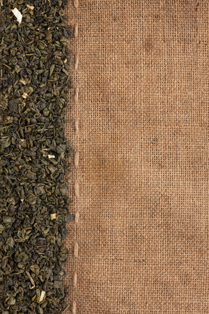 Green tea supplements is on sackcloth, with space for text