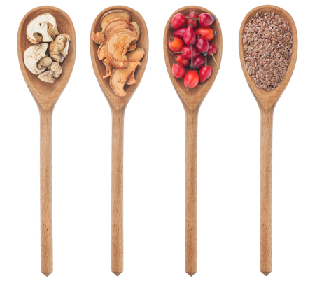 Spoons with flax, mushrooms, wild rose, apple, isolated on white background photo