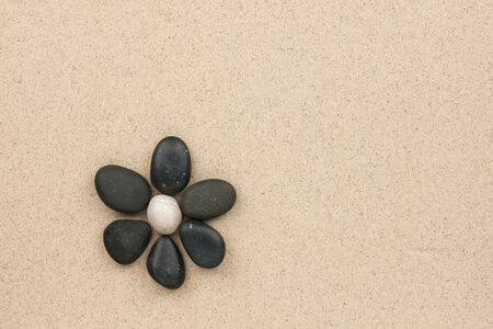 flower made with stones on a sand background  版權商用圖片