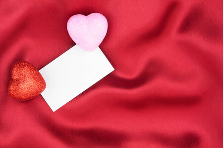 Red and pink  heart with a white card on red background photo