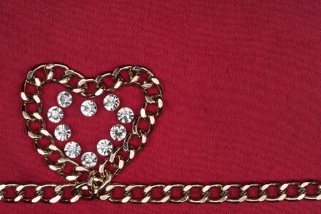 Symbol of heart from the chain and rhinestones on a red background