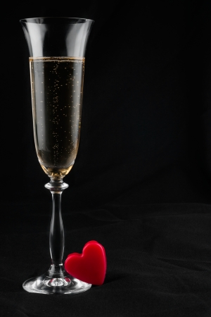 Toasting with champagne and symbolic heart, on a black background  photo