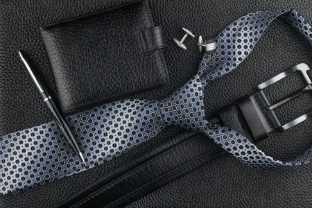 Tie, belt, wallet, cufflinks, pen lying on the skin, can be used as background photo