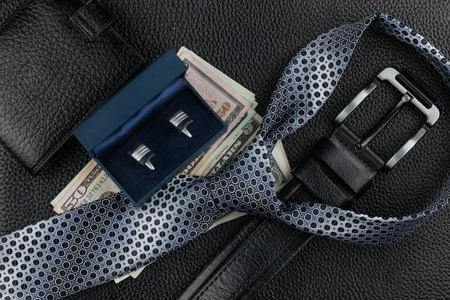 Tie, belt, wallet, cufflinks, money lying on the skin, can be used as background