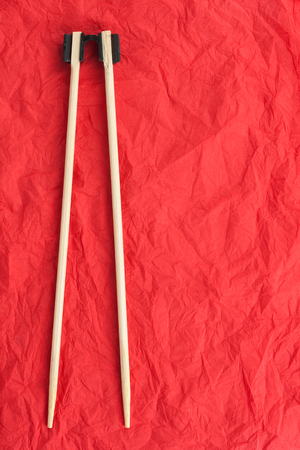 Chopsticks lay on a red napkin photo