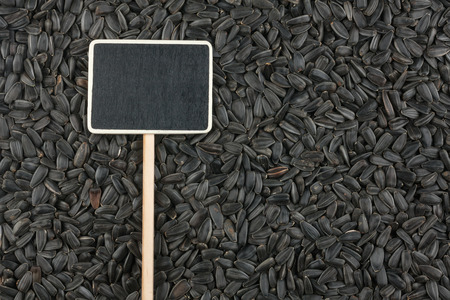 Pointer the price tag lies on sunflower seed, with space for your text Stock Photo