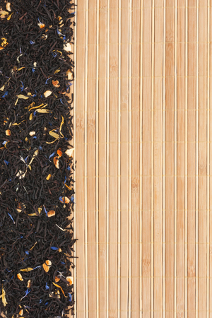 nontraditional: Dried black tea on a bamboo mat, with space for text
