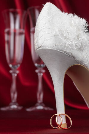 Wedding rings and shoe on red  background and wedding glasses photo