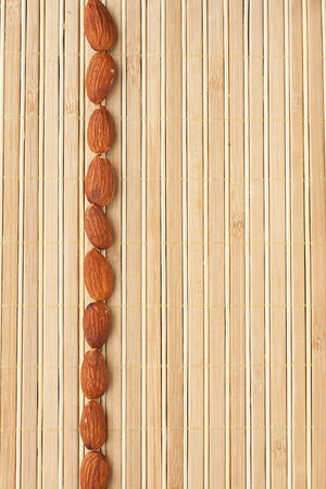 Cases a band of  almond  lying on bamboo mat, as background photo