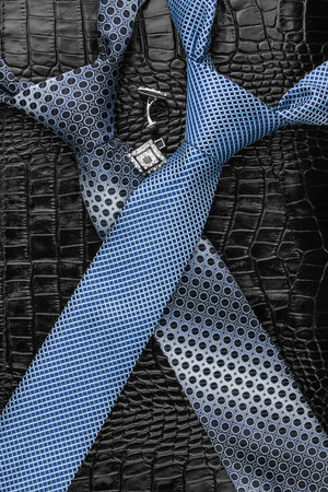 A necktie and  cufflinks  lying on the skin, can be used as background photo