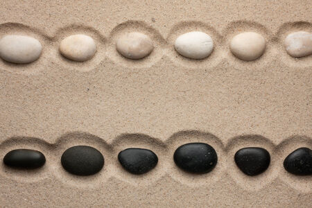 White and black stones lying  in  the sand, with space for your text  photo
