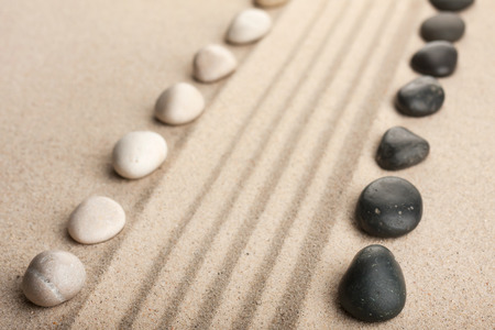 Stripe of white and black stones lying on the sand, can be used as a background photo