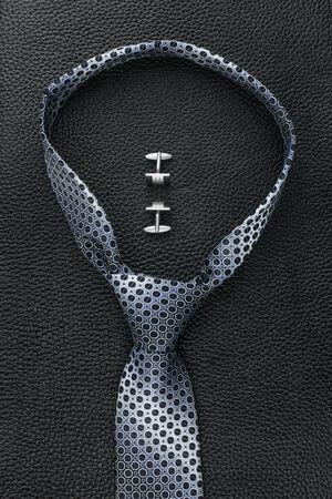 Una cravatta e gemelli sdraiato sulla pelle Archivio Fotografico - 28605862