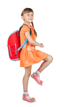 Baby girl with backpack goes to school, isolated on white background